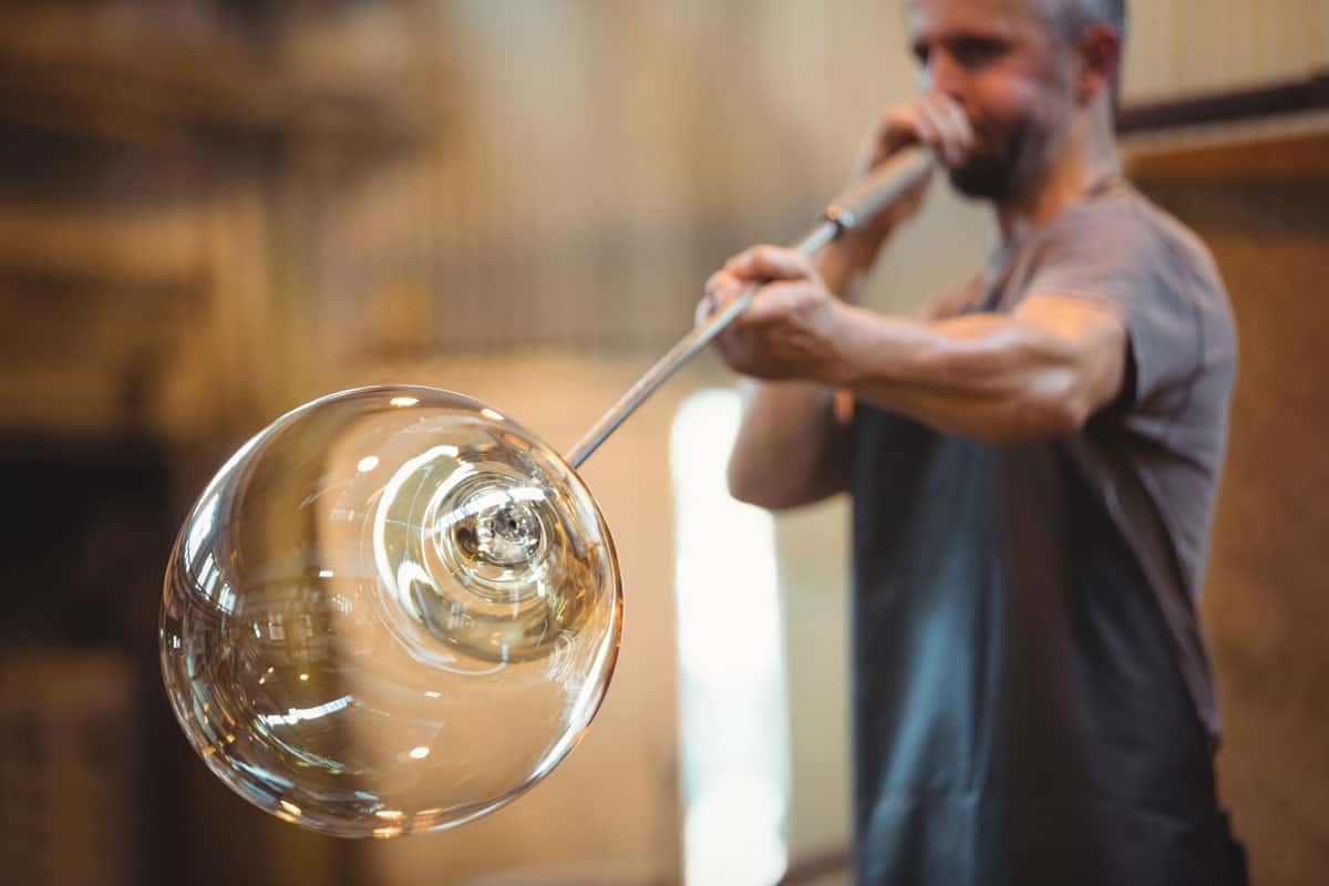 glassblower shaping glass blowpipe